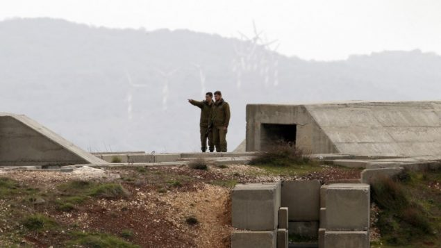 جنود اسرائيليون يراقبون الحدود السورية من موقع عسكري في مرتفعات الجولان، 11 فبراير 2018 (Jalaa Marey/AFP)