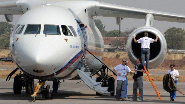 """هذه الصورة من الأرشيف تم التقاطها في 5 مارس، 2010 في حيدر  آباد يظهر فيها تقنيون ومسؤولون وهو يقفون إلى جانب طائرة ركاب من طراز """"أنطونوف  An-148"""" معروضة في معرض الطيران الهندي في مطار """"بوغومبيت"""". (Noah SEELAM / AFP)"""