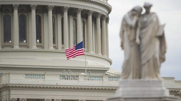تنكيس العلم فوق تلة الكابيتول في العاصمة الأمريكية واشنطن في 15 فبراير، 2018،  في أعقاب إطلاق النار الذي وقع في إحدى مدارس فلوريدا في اليوم السابق. (AFP PHOTO / SAUL LOEB)