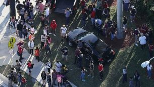 اشخاص ينتظرون خروج احبائهم من مدرسة مارجوري ستونمان دوغلاس الثانوية في باركلاند، فلوريدا، بعد اطلاق النار في المدرسة، 14 فبراير 2018 (Joe Raedle/Getty Images/AFP)