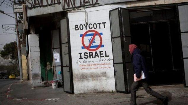 رجل فلسطيني يمر من أمام  رسم على جدار يدعو إلى مقاطعة إسرائيل في أحد شوارع مدينة بيت لحم في الضفة الغربية، 11 فبراير، 2015. (Miriam Alster/Flash 90)