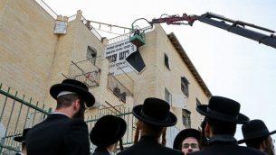 """عمال في بلدية بيت شيمش يزيلون لافتات """"حشمة"""" ف المدينة، 11 ديسمبر 2018 (Yaakov Lederman/Flash90)"""