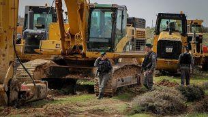 عناصر من شرطة حرس الحدود تقوم بحراسة جرافات خلال الاستعدادات لإخلاء وهدم بؤرة نتيف هأفوت الاستيطانية في 7 فبراير، 2018. (Gershon Elinson/Flash90)