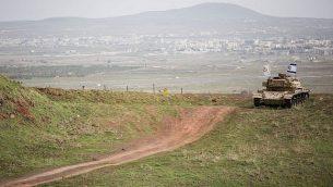 دبابة إسرائيلية قديمة تحمل علما تطل على بلدة القنيطرة السورية في هضبة الجولان، 11 فبراير، 2018. (Hadas Parush/Flash90)