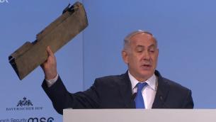 رئيس الوزراء بنيامين نتنياهو يعرض قطعة من طائرة مسيرة إيرانية خلال خطاب في مؤتمر موينيخ الامني، 18 فبراير 2018 (Screen capture)