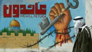 رجل فلسطيني يمر امام جدارية تنادي لعودة اللاجئين الفلسطينيين (Abed Rahim Khatib/Flash90)