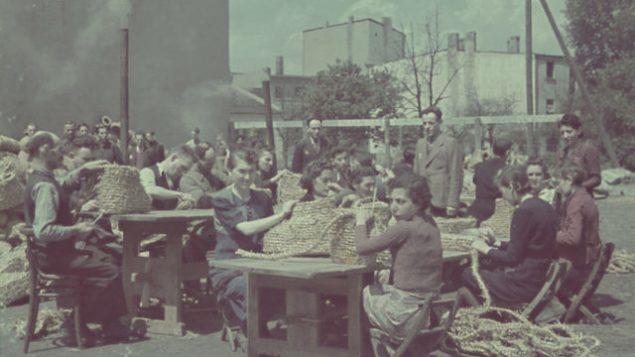 السجناء اليهود في غيتو لودز في بولندا المحتلة على يد النازيين يصنعون السلال . (United States Holocaust Memorial Museum)