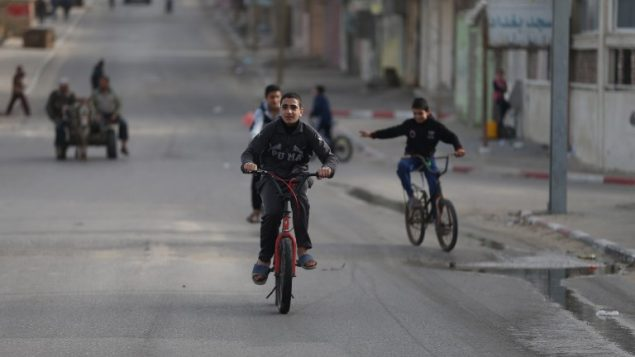 اطفال فلسطينيون يركبون دراجالت هوائية في غزة، 8 مارس 2018 (AFP/ MOHAMMED ABED)