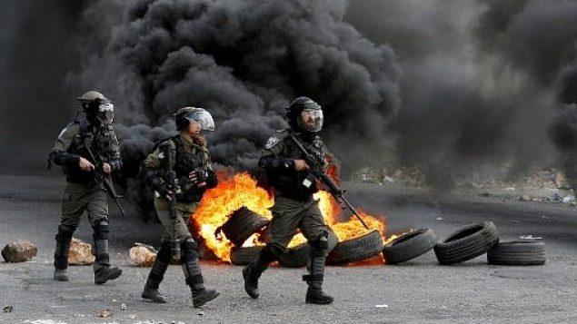 يتقدم حرس الحدود الإسرائيليون في شارع أثناء الاشتباكات مع المتظاهرين الفلسطينيين في أعقاب مظاهرة في مدينة رام الله بالضفة الغربية في 9 مارس 2018 ضد قرار الرئيس الأمريكي دونالد ترامب بالاعتراف بالقدس عاصمة لإسرائيل. (AFP/Abbas Momani)