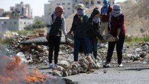 متظاهرات فلسطينيات يحملن الحجارة خلال اشتباكات مع جنود اسرائيليين في بير زيت، الضفة الغربية، 12 مارس 2018 (AFP/ABBAS MOMANI)