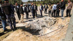 أفراد من قوات الأمن التابعة لحماس يتفقدون الفوهة التي تُركت في موقع الانفجار الذي استهدف موكب رئيس الوزراء الفلسطيني أثناء زيارته لقطاع غزة، بالقرب من معبر إيريز، في 13 مارس / آذار 2018. (AFP PHOTO / MAHMUD HAMS) )