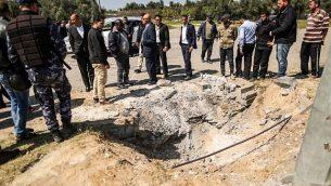 عناصر من قوى الأمن التابعة لحركة حماس تتفقد الفوهة التي خلفها انفجار استهدف موكب رئيس الوزراء الفلسطيني خلال زيارة قام بها إلى غزة بالقرب من معبر إيرز، 13 مارس، 2018. (AFP PHOTO / MAHMUD HAMS)