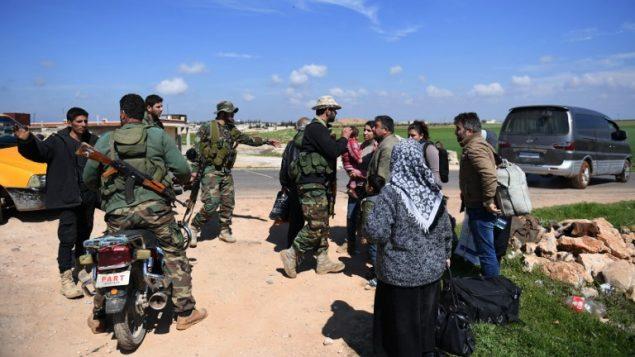 مدنيون يفرون من عفرين مع اعلان تركيا ان جيشها طوق المدينة الكردية في شمال سوريا، 13 مارس 2018 (GEORGE OURFALIAN / AFP)