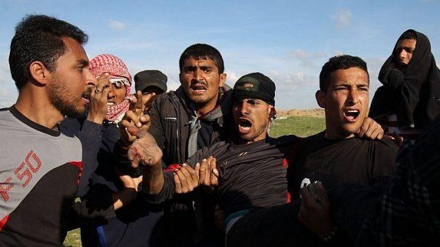 رجال فلسطينيون يحملون متظاهر مصاب خلال اشباكات مع جنود اسرائيليين بالقرب من السياج الحدودي في جنوب قطاع غزة، 16 مارس 2018 (AFP Photo/Said Khatib)