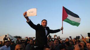 يرفع فلسطينيون عريس وهو يلوح بعلم فلسطيني ويحمل لافتة باسم قرية عائلته في إسرائيل على حدود غزة مع إسرائيل (خلفية)، شرق جباليا، في 29 مارس 2018، قبل معسكر الاحتجاج. ومدته ستة أسابيع. (AFP PHOTO / MAHMUD HAMS)