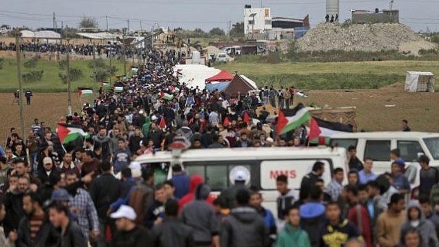 فلسطينيون يسيرون امام مدينة الخيام التي اقيمت امام الحدود مع اسرائيل شرقي مدينة غزة في يوم الارض، 30 مارس 2018 (AFP/ MAHMUD HAMS)