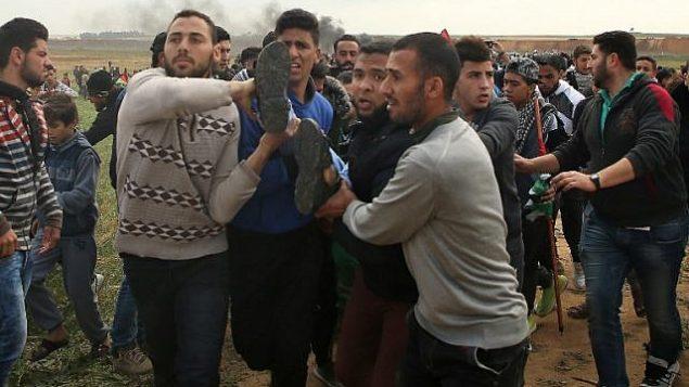 متظاهرون يحملون فلسطيني مصاب اثناء الفرار خلال اشتباكات في مظاهرة بالقرب من الحدود مع اسرائيل شرقي مدينة غزة في يوم الارض، 30 مارس 2018 (AFP/ Mohammed ABED)