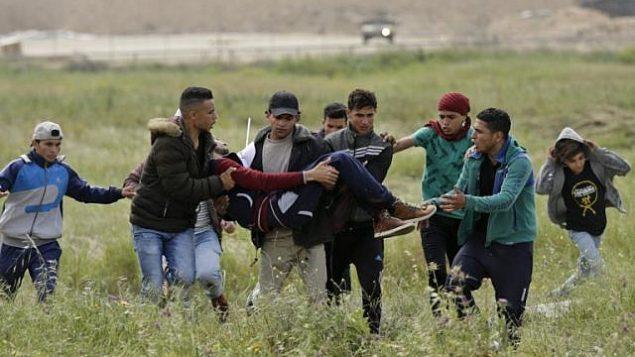 متظاهرون يحملون فلسطيني مصاب اثناء الفرار خلال اشتباكات في مظاهرة بالقرب من الحدود مع اسرائيل شرقي مدينة غزة في يوم الارض، 30 مارس 2018 (AFP/ MAHMUD HAMS)