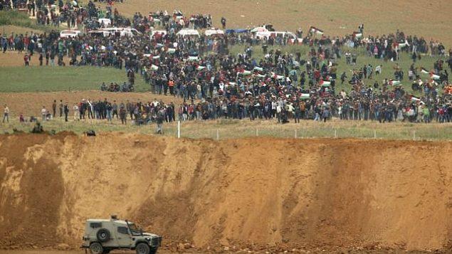 صورة التقطت من كيبوتس ناحال عوز جنوب اسرائيل، يظهر فلسطيني في الطرق الثاني من الحدود يشاركون في مظاهرة في ذكرى يوم الارض، 30 مارس 2018 (AFP PHOTO / Jack GUEZ)