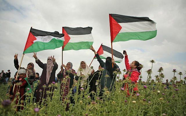 نساء فلسطينيات ترفع الأعلام الفلسطينية وتومض حركة النصر خلال احتجاج بالقرب من الحدود مع إسرائيل شرق جباليا في قطاع غزة في 30 مارس، 2018. (AFP/Mohammed Abed)