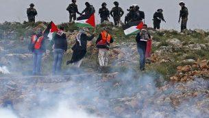 رجال فلسطينيون يرفعون الأعلام أمام القوات الإسرائيلية خلال مظاهرة تخلد ذكرى يوم الأرض في قرية كسرى بالضفة الغربية في 30 مارس / آذار 2018. (AFP/Jaafar Ashtiyeh)