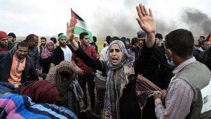 متظاهرون فلسطينيون يلوحون بعلمهم الوطني خلال مظاهرة تخلد ذكرى يوم الأرض، بالقرب من الحدود مع إسرائيل، شرق مدينة غزة  في 30 مارس / آذار 2018. (AFP/Mahmud Hams)