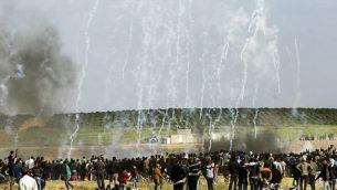 متظاهرون فلسطينيون يفرون بحثاً عن غطاء من الغاز المسيل للدموع الذي أطلقته القوات الإسرائيلية خلال اشتباكات في أعقاب مظاهرة تخلد ذكرى يوم الأرض، قرب الحدود مع إسرائيل، شرق مدينة غزة  في 30 مارس / آذار 2018. (AFP/Mahmud Hams)