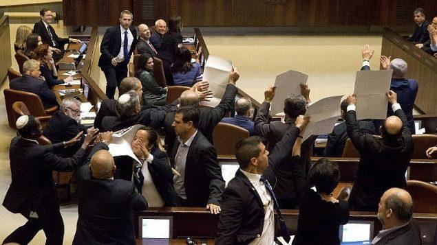 اعضاء كنيست من القائمة العربية المشتركة يرفعون لافتات عليها 'القدس عاصمة فلسطين' خلال خطاب نائب الرئيس الامريكي مايك بنس في الكنيست، 22 يناير 2018 (AFP Photo/Pool/Ariel Schalit)
