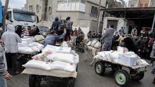 فلسطينيون يجمعون طرود مساعدات في مركز توزيع الغذاء التابع للأمم المتحدة في خان يونس الواقعة جنوب قطاع غزة، 28 يناير، 2018. (Said Khatib/AFP)
