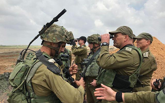يقف رئيس القيادة الجنوبية للجيش الإسرائيلي، اللواء إيال زامير، من خلال منظارين للحصول على رؤية أفضل لقطاع غزة، حيث يقف رئيس عمليات الجيش الإسرائيلي، اللواء نيتسان ألون، خلفه خلال احتجاج جماعي على طول الحدود في 30 مارس، 2018. (الجيش الإسرائيلي)
