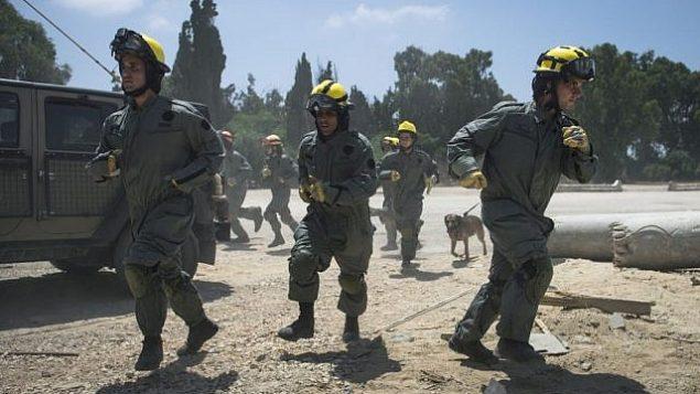 جنود في وحدات البحث والإنقاذ التابعة لقيادة الجبهة الداخلية في الجيش الإسرائيلي يهرعون إلى موقع يحاكي موقع هجوم صاروخي خلال مناورة عسكرية واسعة النطاق في زيكيم بالقرب من الحدود مع غزة في 3 يوليو، 2016. (وحدة المتحدث باسم الجيش الإسرائيلي)