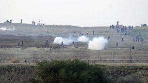 توضيحية: متظاهرون فلسطينيون بالقرب من السياج الحدود الإسراءئيلي مع قطاع غزة والجيش الإسرائيلي يطلق قنابل الغاز المسيل للدموع باتجاههم، 3 يناير، 2014. (David Buimovitch/Flash90)