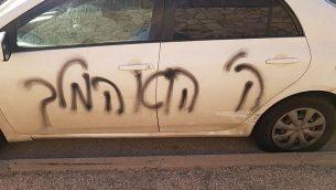 عبارة 'الرب هو الملك' باللغة العبرية التي تم خطها على مركبة في حي بيسغات زئيف اليهودي في القدس الشرقية، 19 مارس، 2018. (المتحدث باسم الشرطة الإسرائيلية)