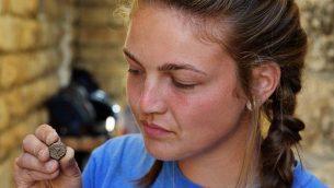 تحمل طالبة من كلية أرمسترونغ عملة تم اكتشافها في الحفريات الأثرية في أوفيل خارج أسوار مدينة القدس القديمة، حيث اكتشفت مؤخرًا مجموعة من العملات البرونزية النادرة من الثورة اليهودية، ويعود تاريخها إلى حوالي 66-70.(Eilat Mazar)