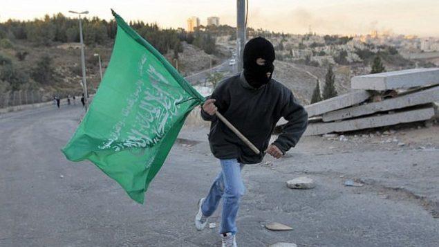 شاب من القدس يحمل علم حماس. (Nati Shohat/Flash90)