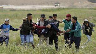 متظاهرون يحملون شابا فلسطينيا أصيب خلال المواجهات، في أعقاب مظاهرة أجريت بالقرب من الحدود مع إسرائيل شرق مدينة غزة لإحياء ذكرى 'يوم الأرض'، 30 مارس، 2018. (AFP/ MAHMUD HAMS)