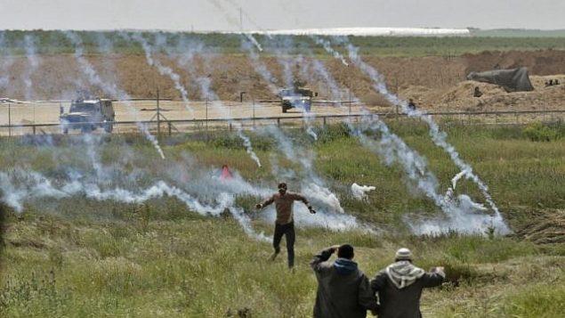 صورة تم التقاطها في 30 مارس، 2018 تظهر فلسطينيين يفرون من قنابل الغاز المسيل للدموع خلال تظاهرة بالقرب من السياج الحدودي مع إسرائيل، شرقي مدينة غزة. (AFP/Mahmud Hams)