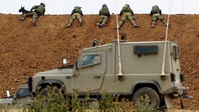 جنود إسرائيليون يتخذون هدف وهم يرقدون على حاجز ترابي على طول الحدود مع قطاع غزة، بالقرب من ناحال عوز الكيبوتس في جنوب إسرائيل في 30 مارس  2018.(Jack Guez/AFP)