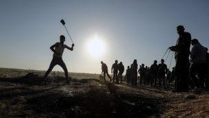 متظاهر فلسطيني يقذف الحجارة باتجاه الجنود الإسرائيليين خلال مظاهرة عند الحدود مع إسرائيل، شرقي مدينة غزة، 31 مارس، 2018.  (AFP PHOTO / MAHMUD HAMS)