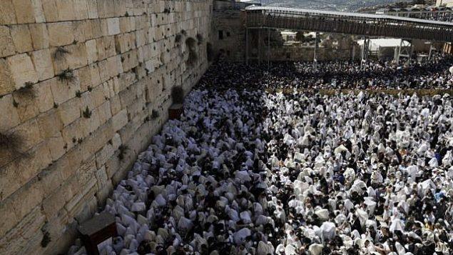يهود يرتدون شالات الصلاة يشاركون في صلاة 'بركة الكهنة' خلال عيد الفصح اليهودي في الحائط الغربي في البلدة القديمة في القدس، 2 أبريل، 2018. ( AFP PHOTO / MENAHEM KAHANA)
