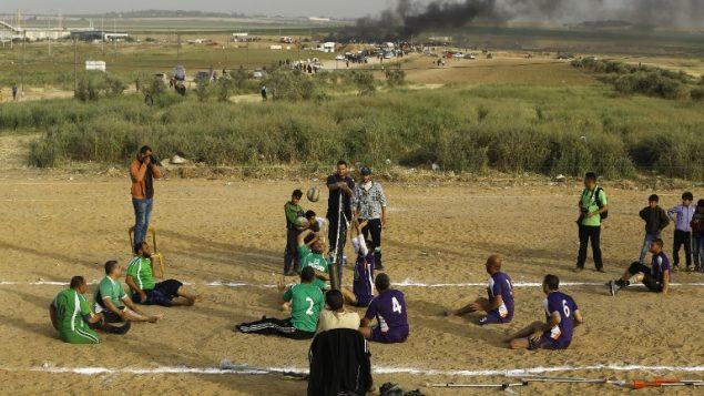 فلسطينيون ذوي اعاقات يلعبون الكرة الطائرة بالقرب من موقع الاشتباكات بين متظاهرين فلسطينيين وقوات الامن الإسرائيلية في اعقاب مظاهرات امام الحدود بين غزة واسرائيل، شرقي مدينة غزة، 5 ابريل 2018 (AFP/MOHAMMED ABED)