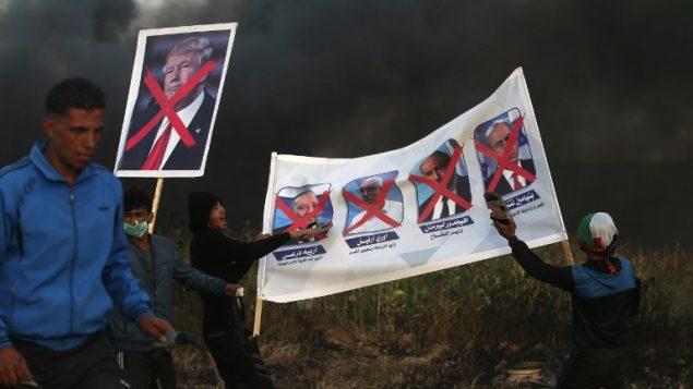 متظاهرون فلسطينيون يحملون لافتات عليها صور سياسيين اسرائيليين والرئيس الامريكي دونالد ترامب خلال اشتباكات مع قوات الامن الإسرائيلية في اعقاب مظاهرة امام الحدود مع اسرائيل، شرقي مدينة غزة، 5 ابريل 2018 (AFP PHOTO / MOHAMMED ABED)