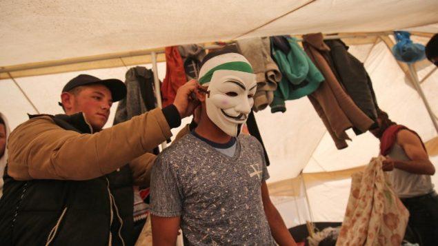 رجل فلسطيني يرتدي قناع تجهيزا لمظاهرات امام الحدود بين غزة واسرائيل بالقرب من خان يونس، شرقي مدينة غزة، 6 ابريل 2018 (SAID KHATIB / AFP)