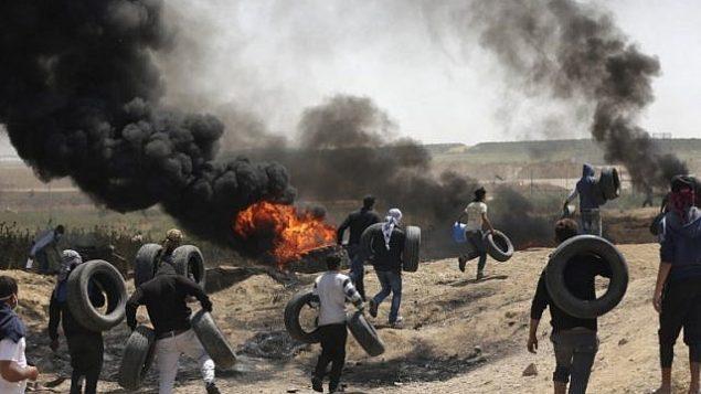 فلسطينيون يشعلون الاطارات للحماية من القناصين الإسرائيليين خلال اشتباكات عند الحدود بين غزة واسرائيل، 6 ابريل 2018 (MAHMUD HAMS / AFP)
