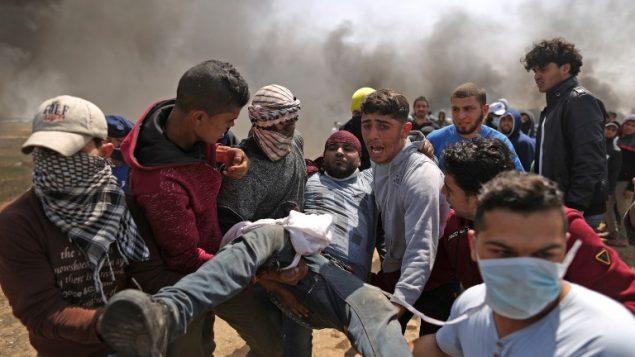 رجال فلسطينيون يحملون متظاهر مصاب خلال اشتباكات مع القوات الإسرائيلية امام الحدود بين غزة واسرائيل، شرقي مدينة غزة، 6 ابريل 2018 (MAHMUD HAMS / AFP)