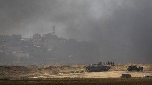 نشر قوات إسرائيلية بالقرب من كيبوتس نير عوز  بالقرب من حدود إسرائيل مع غزة وسط دخان يتصاعد جراء حرق إطارات من قبل فلسطينيين بالقرب من مدينة خان يونس في الجزء الجنوبي من قطاع غزة، 6 أبريل، 2018. (AFP PHOTO / Menahem KAHANA)