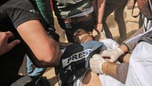 الصحفي الفلسطيني ياسر المرتجى بعد اصابته خلال اشتباكات مع القوات الإسرائيلية امام الحدود بني غزة واسرائيل، 6 ابريل 2018 (AFP/Said Khatib)