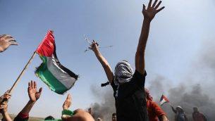 متظاهرون فلسطينيون يلوحون بعلمهم الوطني ويرددون هتافات ضد قوات الأمن الإسرائيلية خلال احتجاج على الحدود بين إسرائيل وغزة في شمال قطاع غزة في 6 أبريل / نيسان 2018. (AFP/Mohammed Abed)