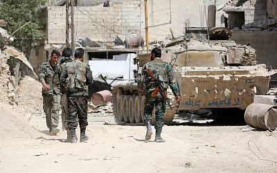 صورة تم التقاطها في 8 أبريل، 2018، يظهر فيها جنود في الجيش السوري يحتشدون في منطقة في الأطراف الشرقية لمدينة دوما، مع استمرار هجومهم آخر معاقل المتمردين الغوطة الشرقية.  (AFP Photo/Stringer)