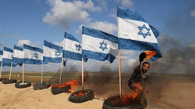 متظاهر فلسطيني يستعد لحرق أعلام إسرائيلية في 10 أبريل، 2018 في موقع الاحتجاجات بالقرب من الحدود بين غزة وإسرائيل شرق جباليا في شمال قطاع غزة. (AFP PHOTO / Mohammed ABED)